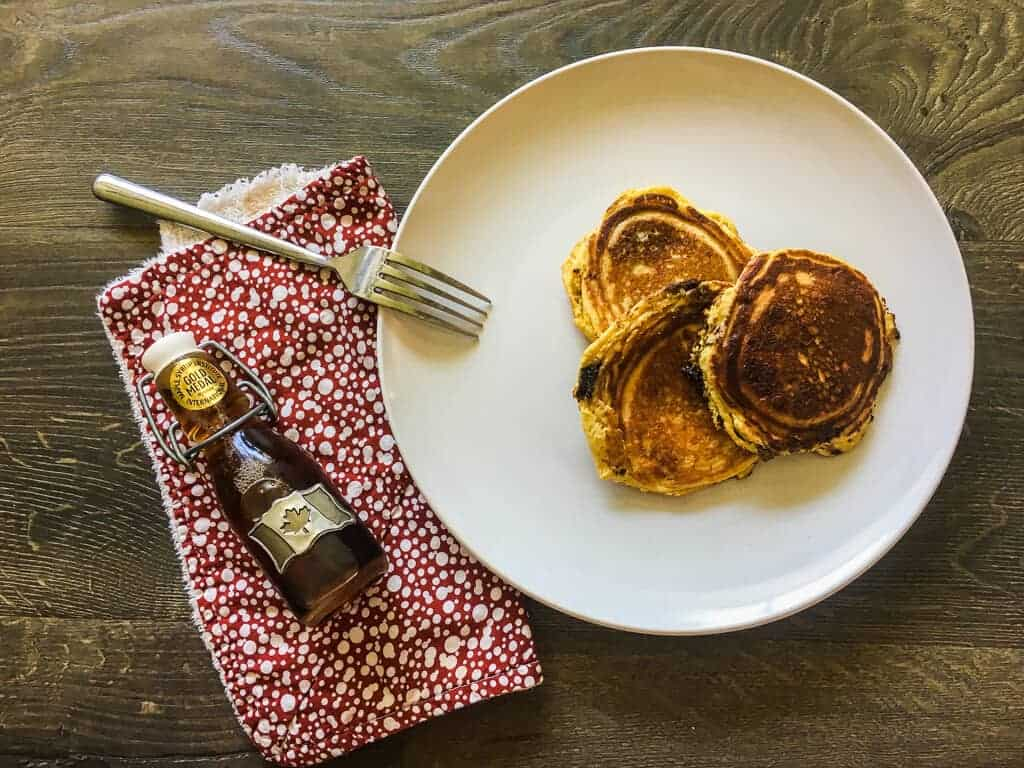 A white plate with three paleo pancakes and a red napkin with a small bottle of maple syrup.
