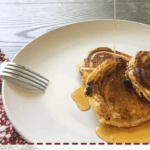 Three chocolate chip paleo pancakes on a white dish being drizzled with maple syrup.