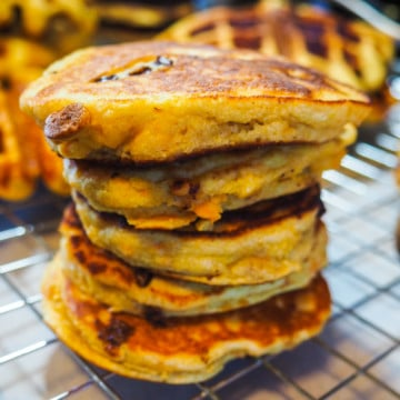 A stack of paleo sweet potato chocolate chip pancakes and waffles on a cooling rack.