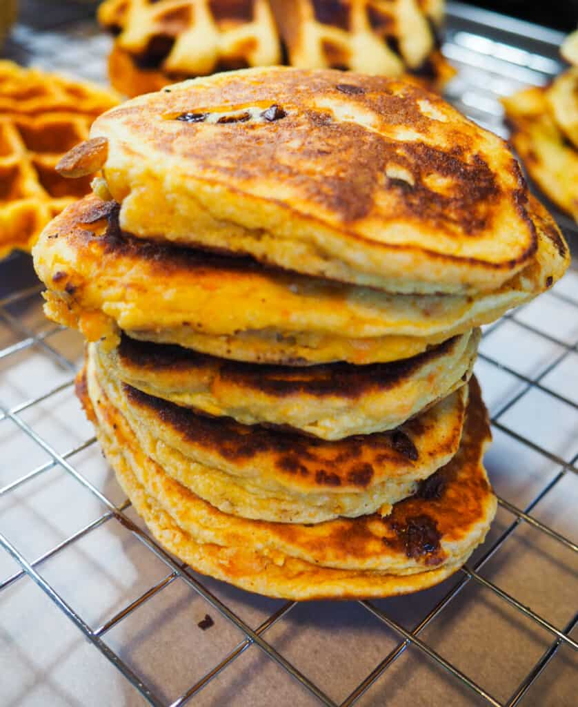 A stack of paleo sweet potato pancakes and waffles on a cooling rack.