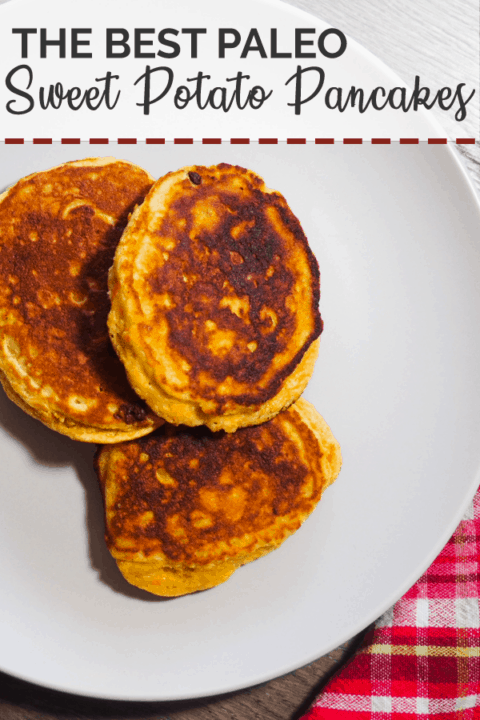 Three sweet potato paleo pancakes on a white plate with a red checkered napkin and small bottle of maple syrup.