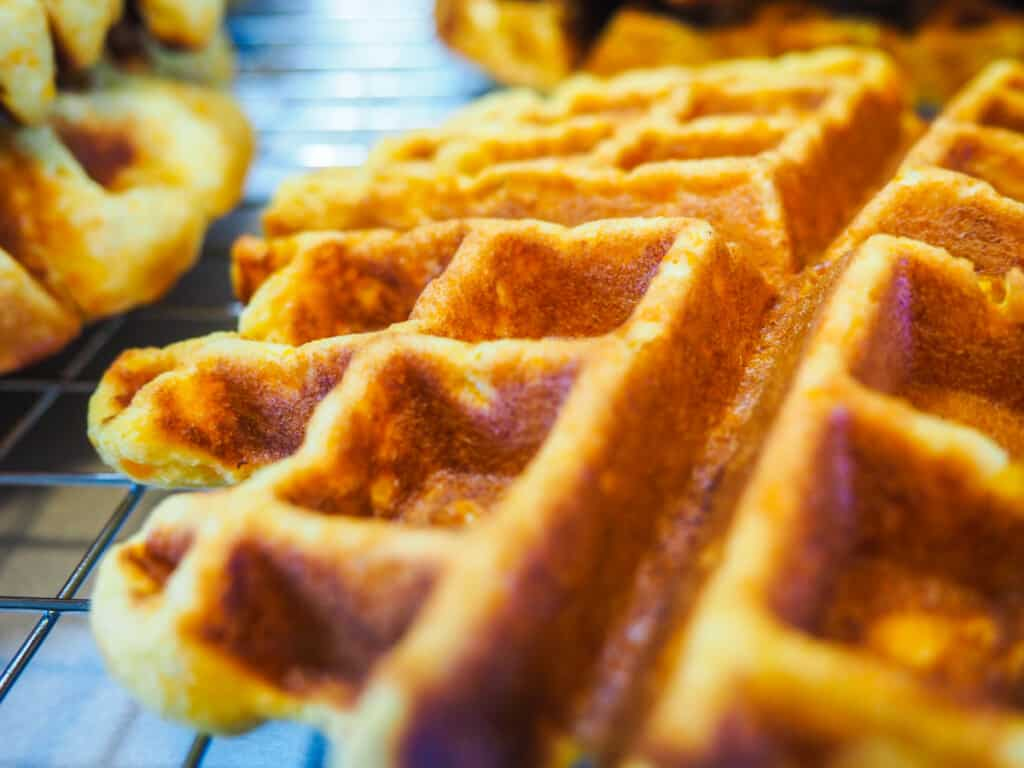 A close up image of a paleo sweet potato waffle on a cooling rack.