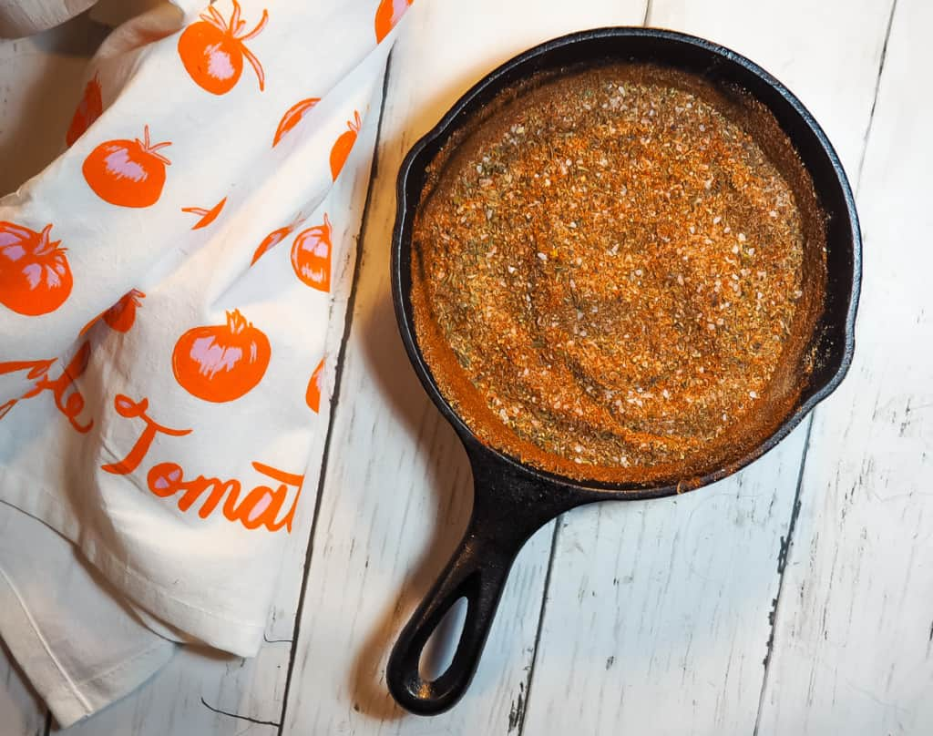 A small cast iron pan with the mixed ingredients of cajun seasoning mix in it.