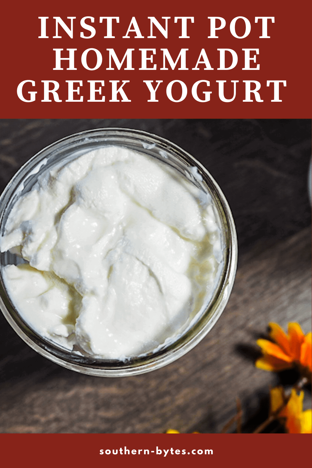 A pin image of a mason jar full of homemade yogurt and a yellow flower on a gray wood background.