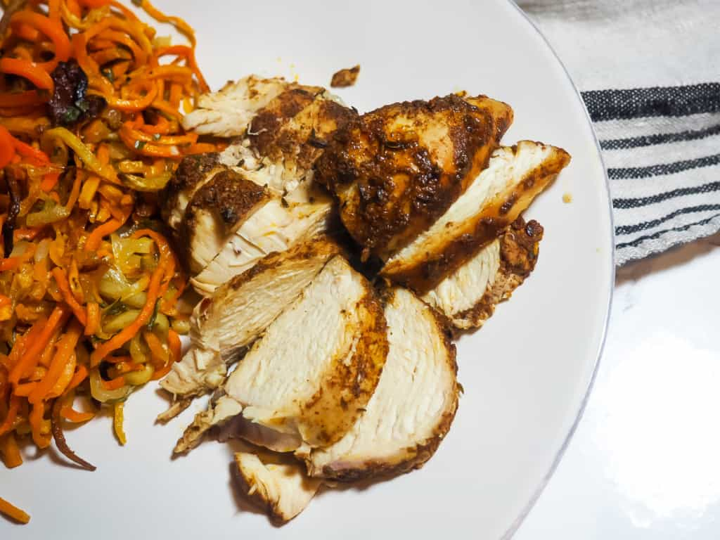 A left aligned white plate with crispy sweet potato noodles and sliced Jamaican Jerk Chicken with a gray and navy dish towel.