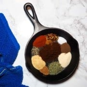 A small black cast iron pan with the unmixed ingredients for making Jamaican Jerk Seasoning and a blue dish cloth.