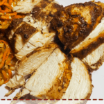 A zoomed in pin image of a white plate with crispy sweet potato noodles and sliced Jamaican Jerk Chicken.
