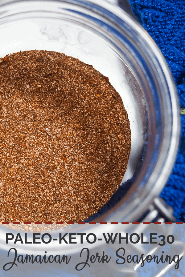 A pin image of a small jar with the mixed ingredients of Jamaican Jerk Seasoning (zoomed in) and a blue dish cloth.