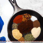 A pin image of a small cast iron pan with the unmixed ingredients for making Jamaican Jerk Seasoning and a blue dish cloth.