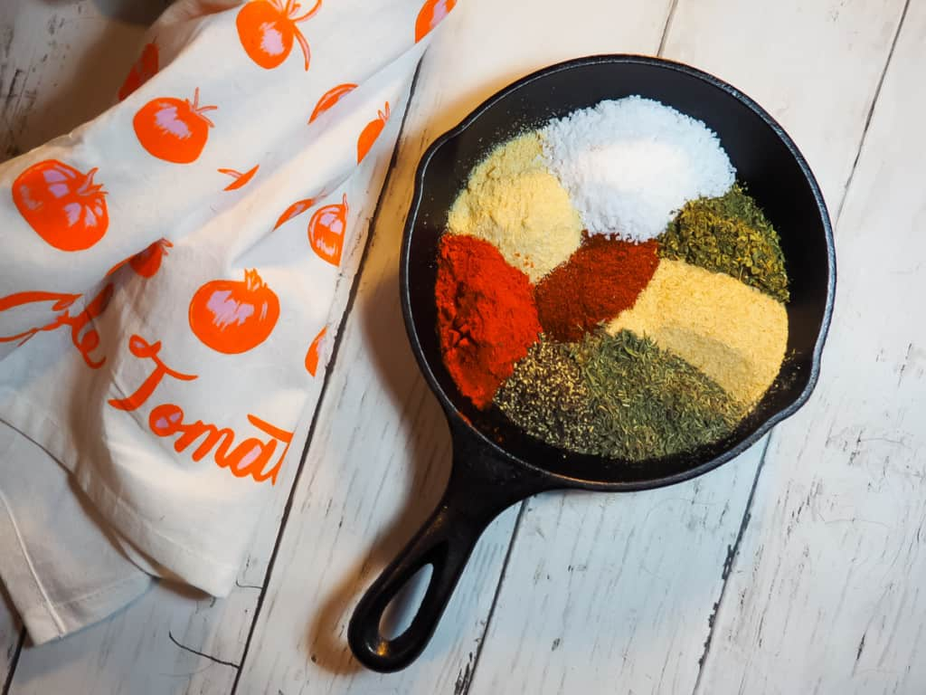 A small cast iron pan with the sorted ingredients of cajun seasoning mix in it.
