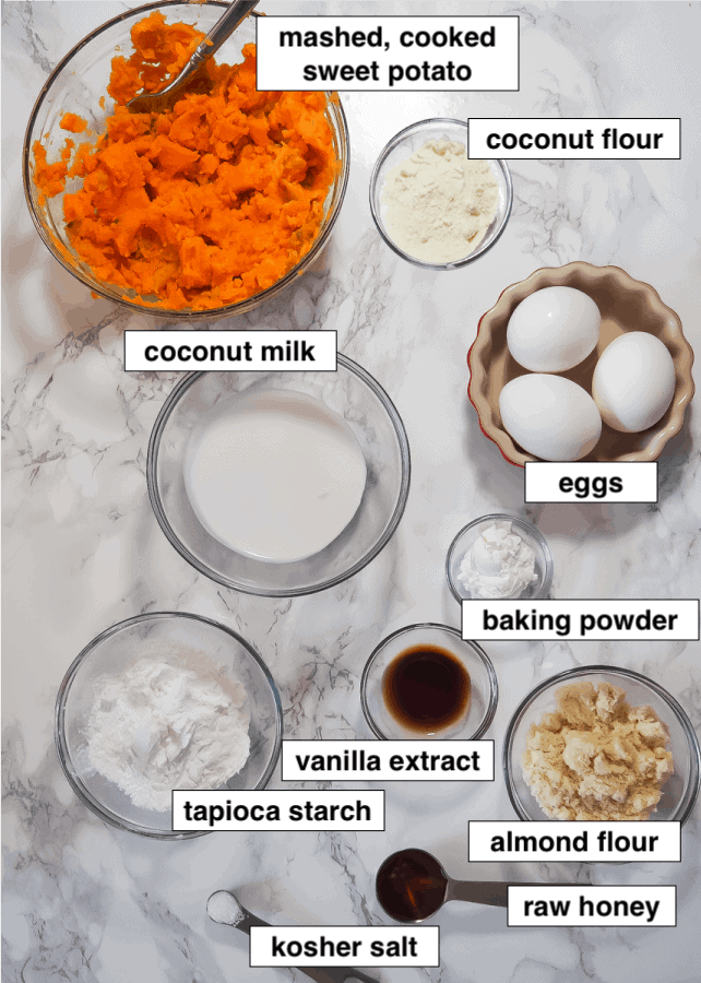 A marble board with the labeled ingredients for paleo sweet potato pancakes. Mashed sweet potato, almond flour, coconut flour, honey, coconut milk, tapioca starch, salt, eggs, vanilla extract, and baking powder.