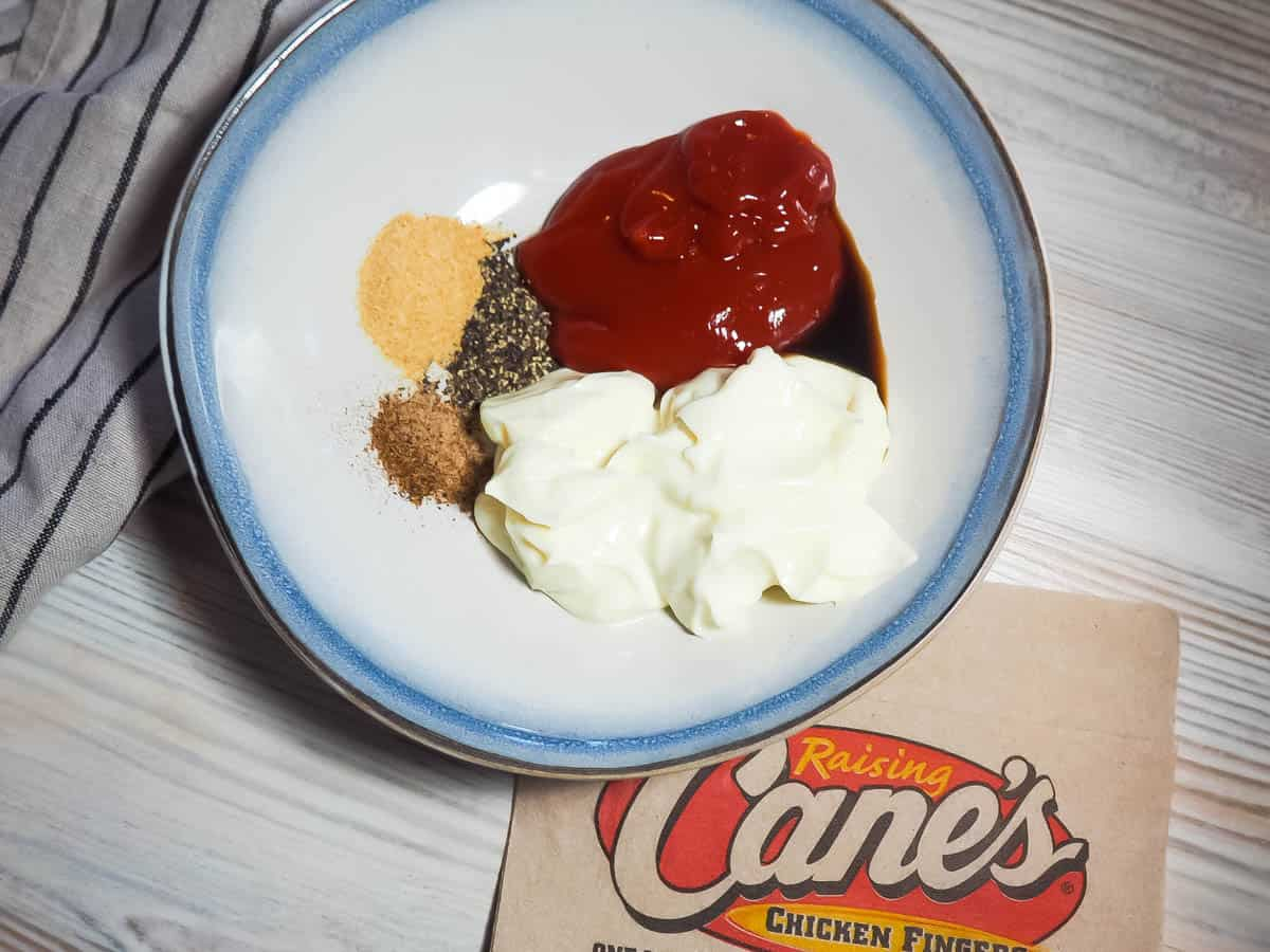 A blue and white bowl of the unmixed ingredients of Raising Cane's dipping sauce with a red spatula and a Cane's napkin.