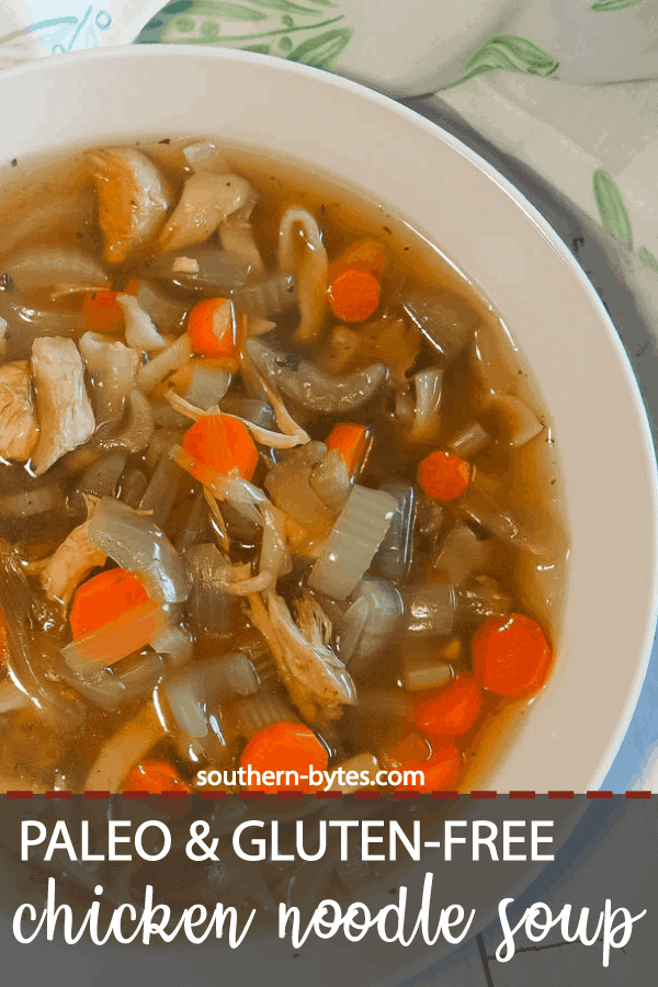 A pin image of a white bowl of paleo chicken noodle soup with carrots, celery, and onions on a white wooden background with a blue and white tea towel.