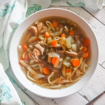 A white bowl of paleo chicken noodle soup with carrots, celery, and onions on a white wooden background with a spoon and blue and white tea towel.