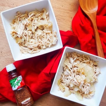 Two white bowls of shredded chicken and onions with chili lime seasoning with a red cloth napkin and a bottle of Tajin seasoning on a wooden background.