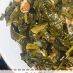 A pin image of a white bowl of cooked paleo collard greens with bits of bacon.