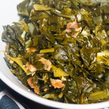 A white bowl of paleo collard greens with bits of bacon on a blue and white towel.
