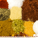 A pin image of the ingredients in taco seasoning in a bowl, unmixed.