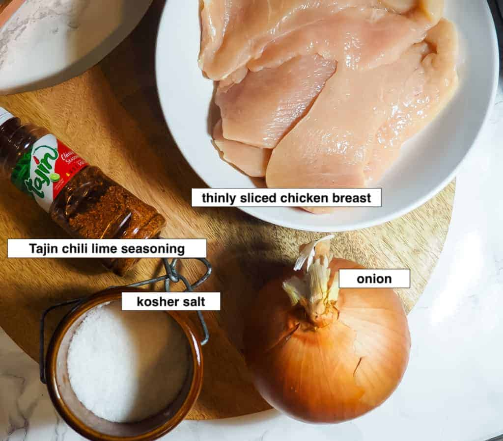 An image of ingredients for chili lime chicken - Tajin seasoning, kosher salt, onion, and sliced chicken breast.