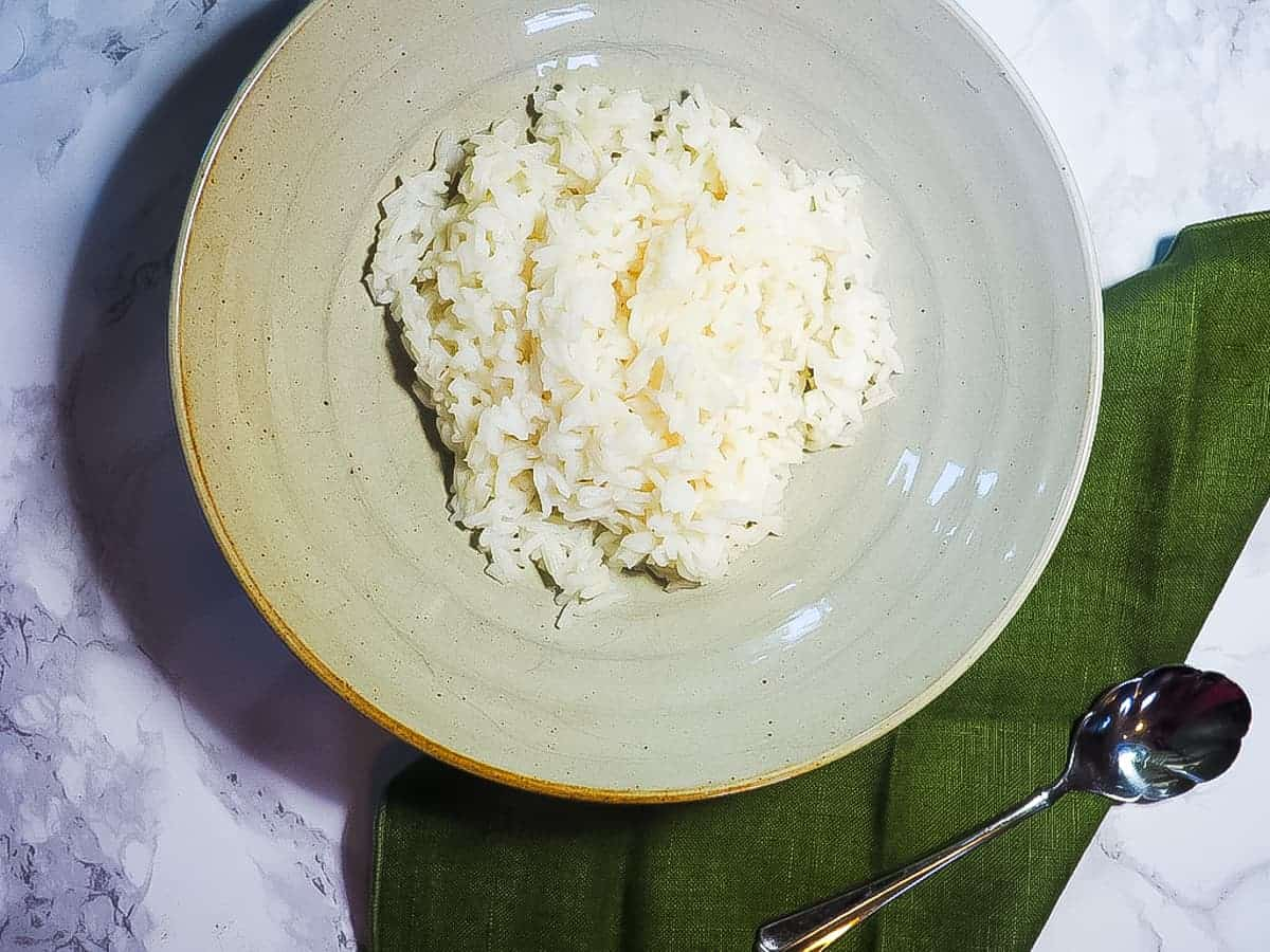 A bowl of white rice on a marble background with a green napkin and a spoon.