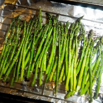 A sheet pan covered in foil with oven roasted asparagus.