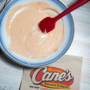 A pin image blue and white bowl of orange Raising Cane's dipping sauce with a red spatula and a Cane's napkin.