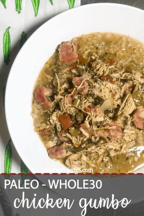A pin image of a white bowl of paleo chicken and sausage gumbo on top of a tea towel covered in little okra.