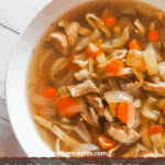 A pin image of a white bowl of paleo chicken noodle soup with carrots, celery, and onions on a white wooden background.
