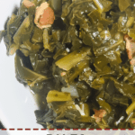 A pin image of a white bowl of cooked paleo collard greens with bits of bacon and salt.