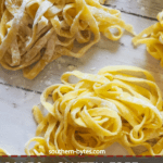 A pin image of piles of homemade paleo pasta on a white wooden board.
