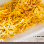 A pin image of a large clear tupperware filled with homemade paleo pasta and a tea towel with a turquoise pattern and a white wood board.