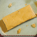 A peanut butter perfect bar on a gray plate with a red napkin and a white flower.