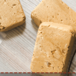 A pin image of a pile of peanut butter perfect bars on a gray background.