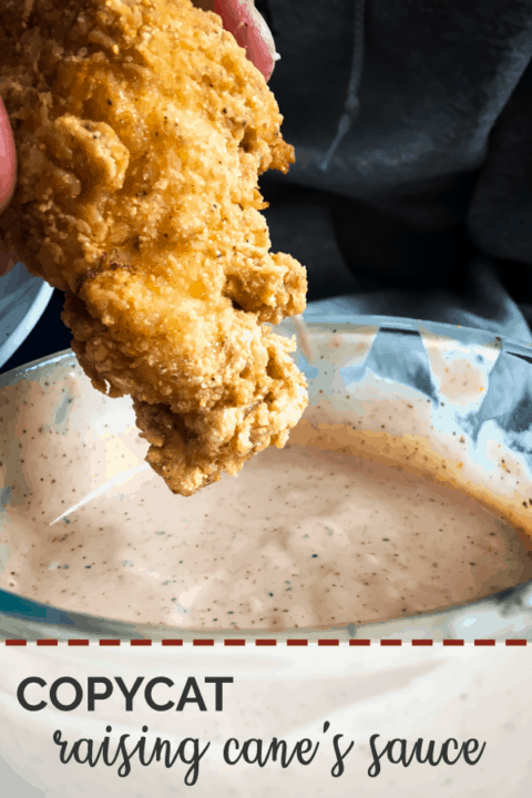 A pin image of a fried chicken tender being dunked in orange Raising Cane's Sauce