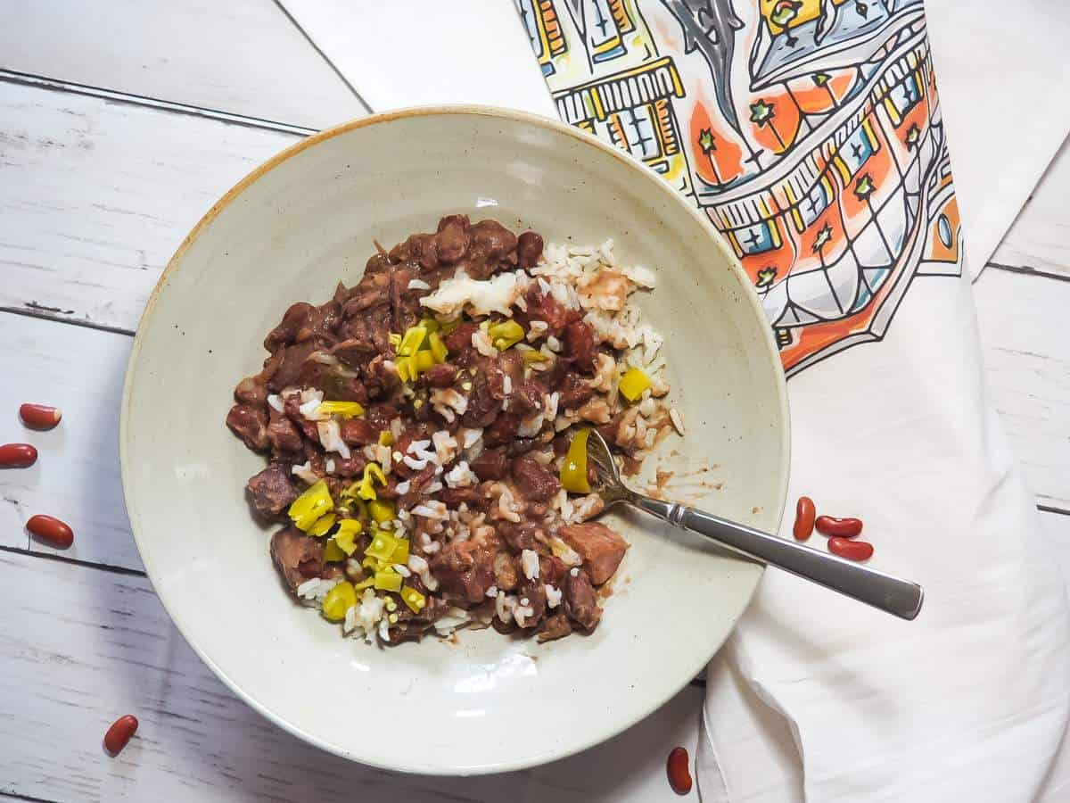 A bowl of red beans, rice, and sausage with pepperoncini peppers and a New Orleans dish towel.