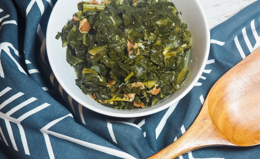 A white bowl of collard greens with bits of bacon on a blue and white towel with a wooden spoon.