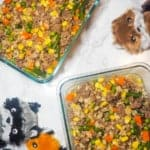 Two glass containers of homemade dog food on a marble background with three dog toys.