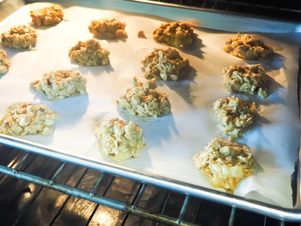 A cookie sheet covered in peanut butter dog treats in the oven.