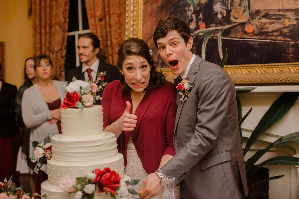 A newly married couple making stupid faces while cutting their wedding cake.