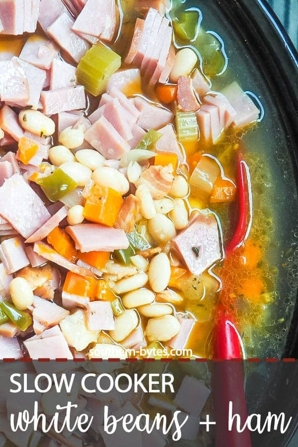A pin image of a crockpot filled with white beans and ham, cooking.