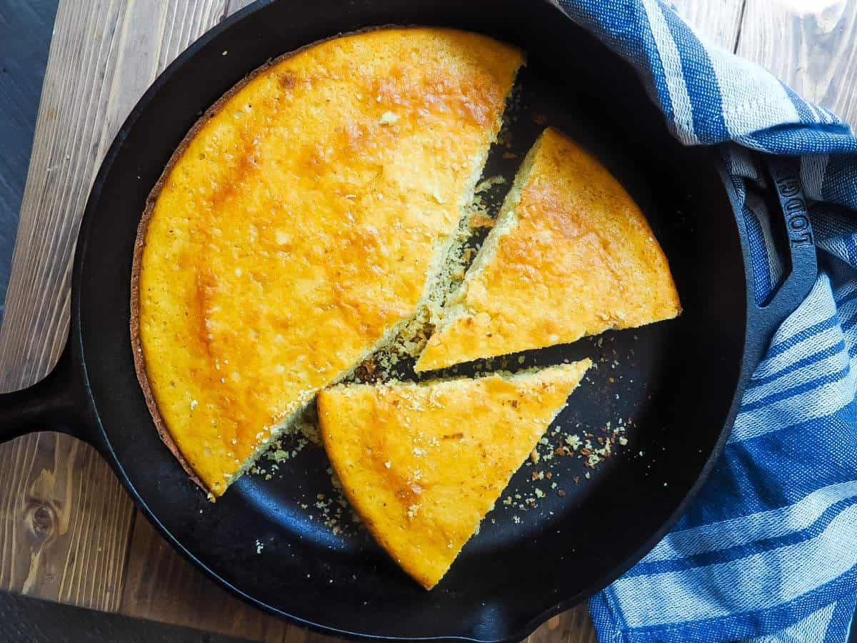 A cast iron skillet with slices of cornbread in it.