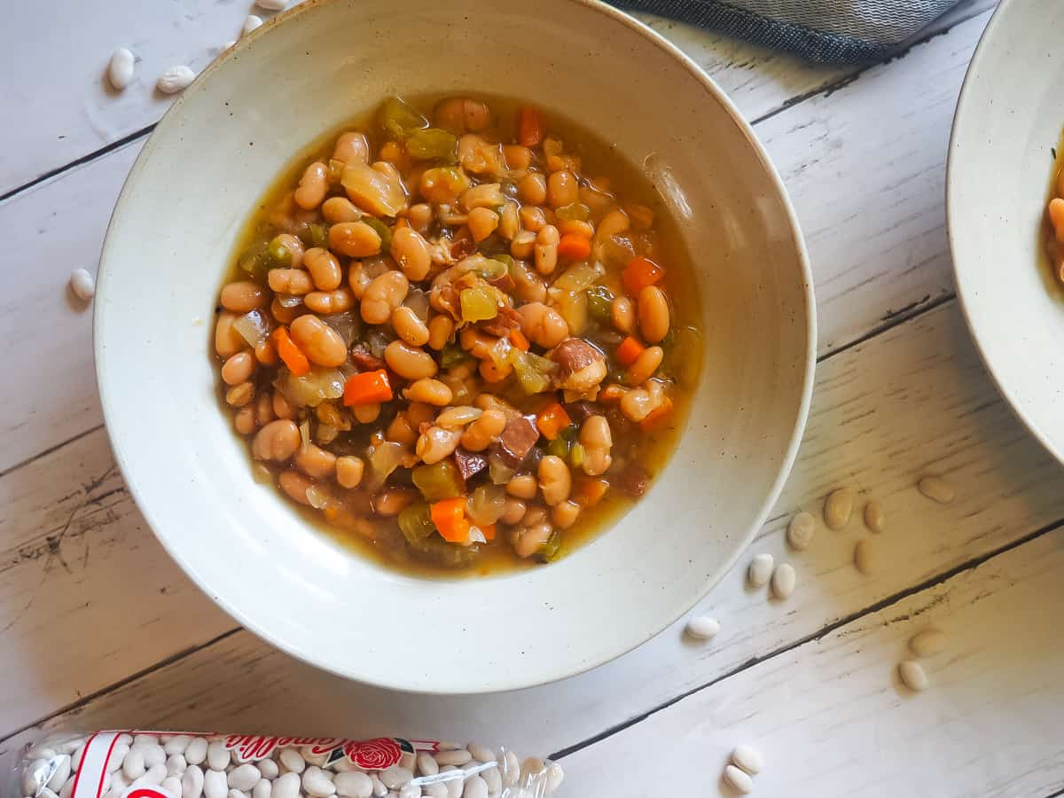 A bowl of white beans and ham with Camellia beans spread around it.