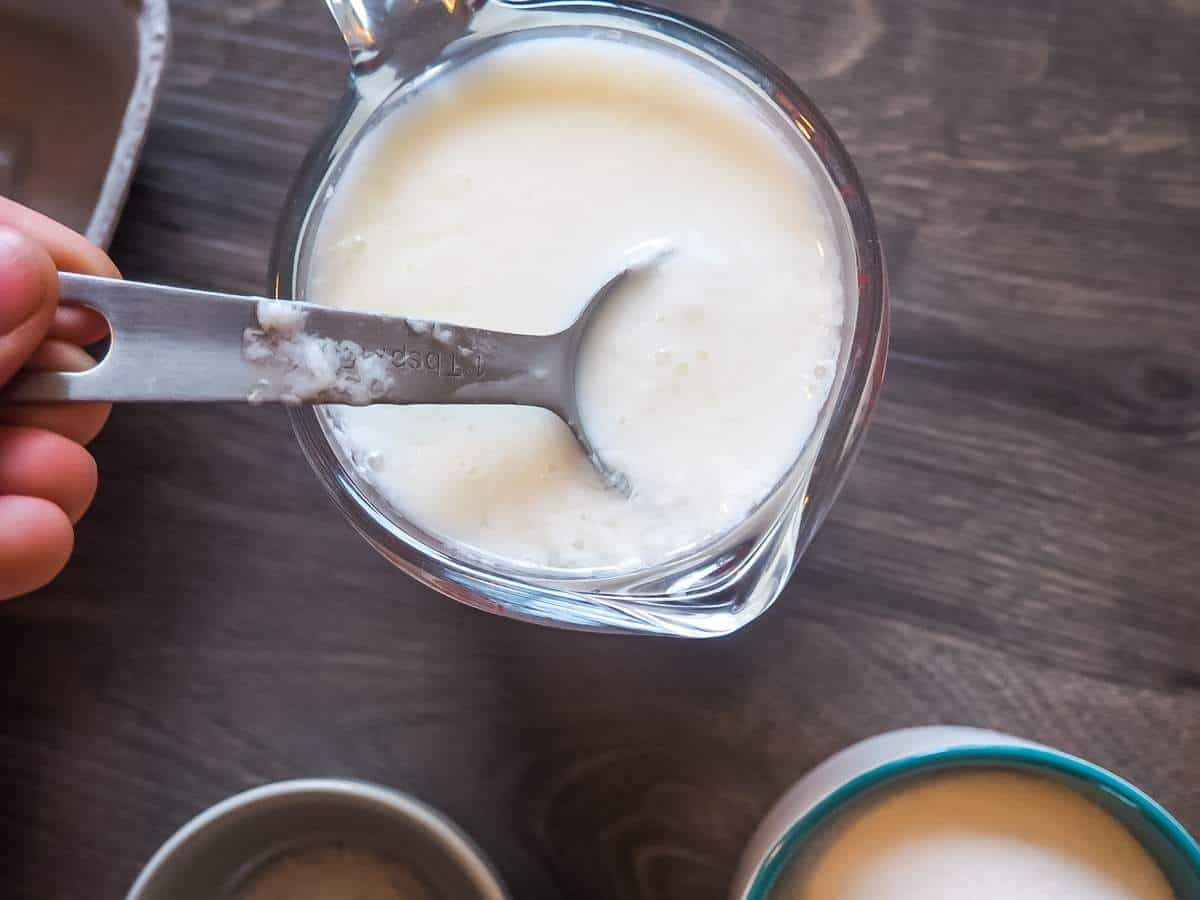 A spoon scooping curdled milk out of a measuring cup to make faux buttermilk.