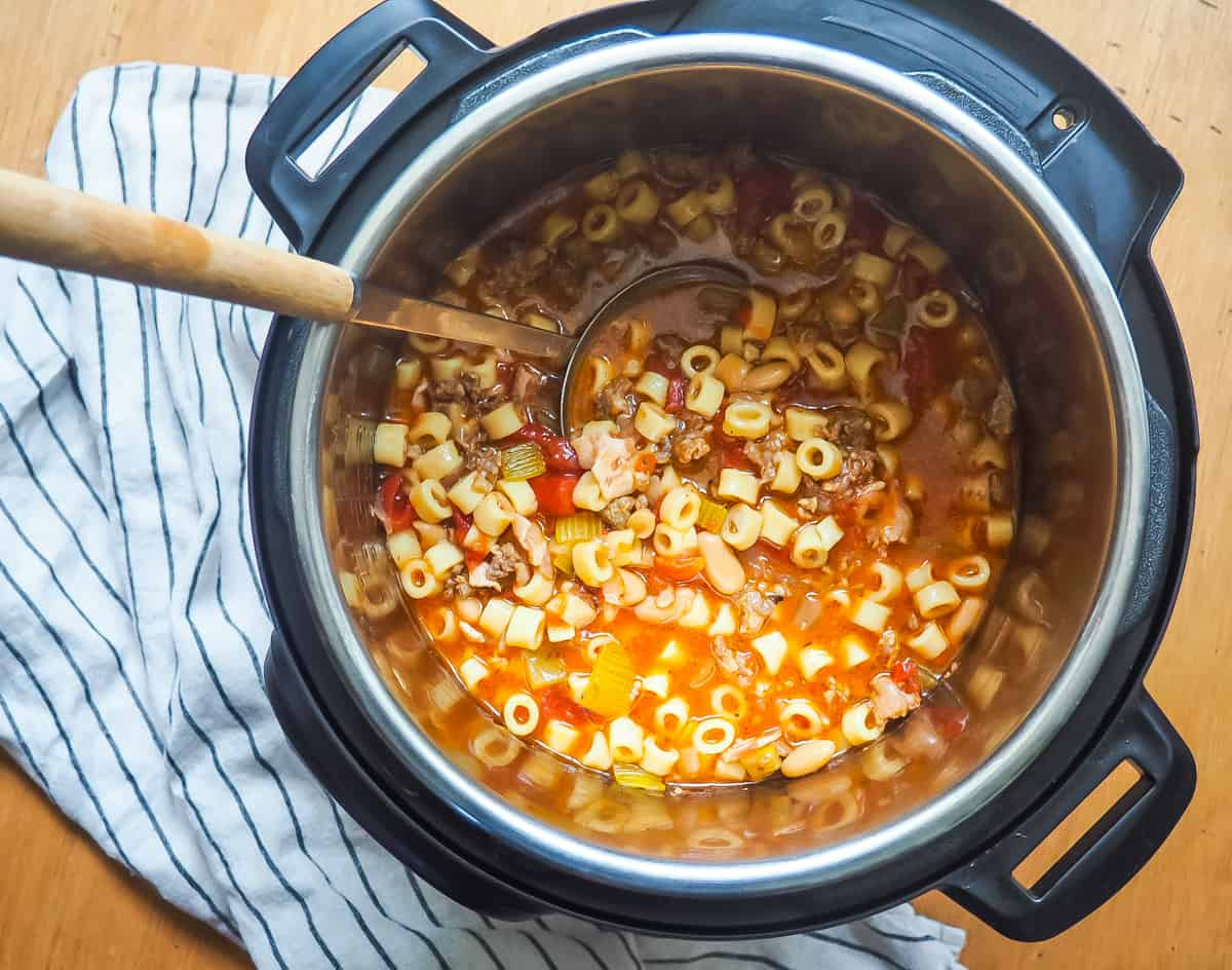 A instant pot of pasta e fagioli with a ladle scooping some out.