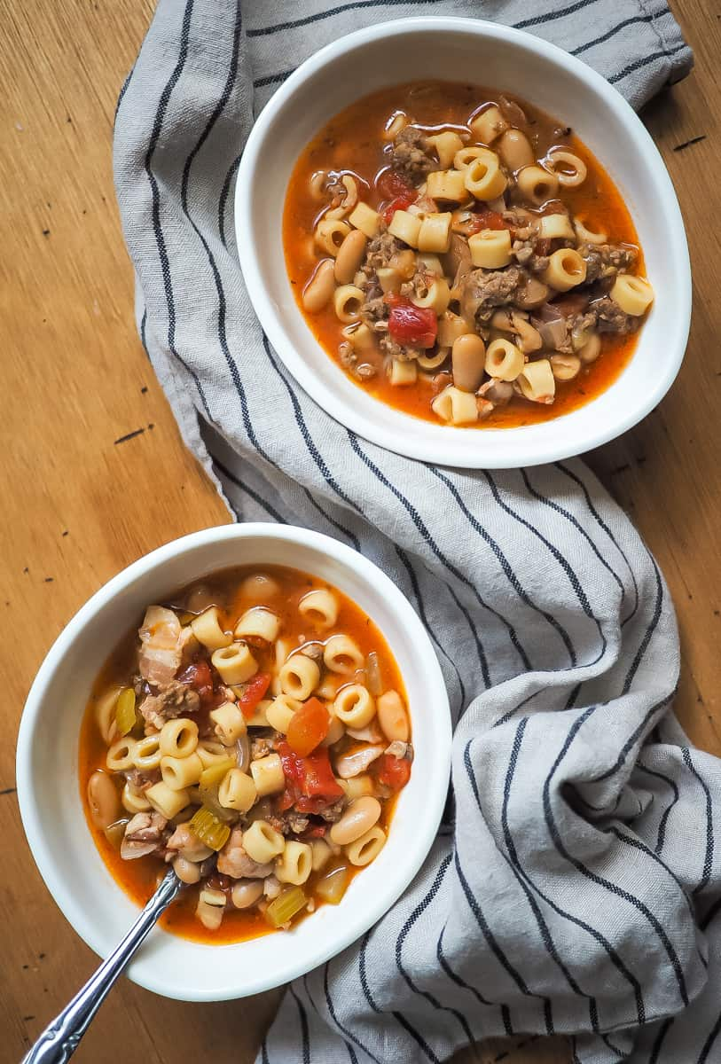Two white bowls of pasta e fagioli on wooden background.