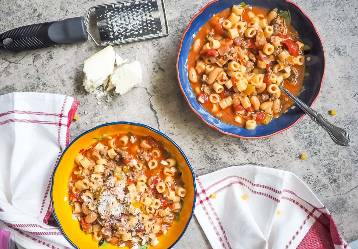 Yellow and blue bowls of pasta e fagioli with a spoon and a block of parmesan cheese.