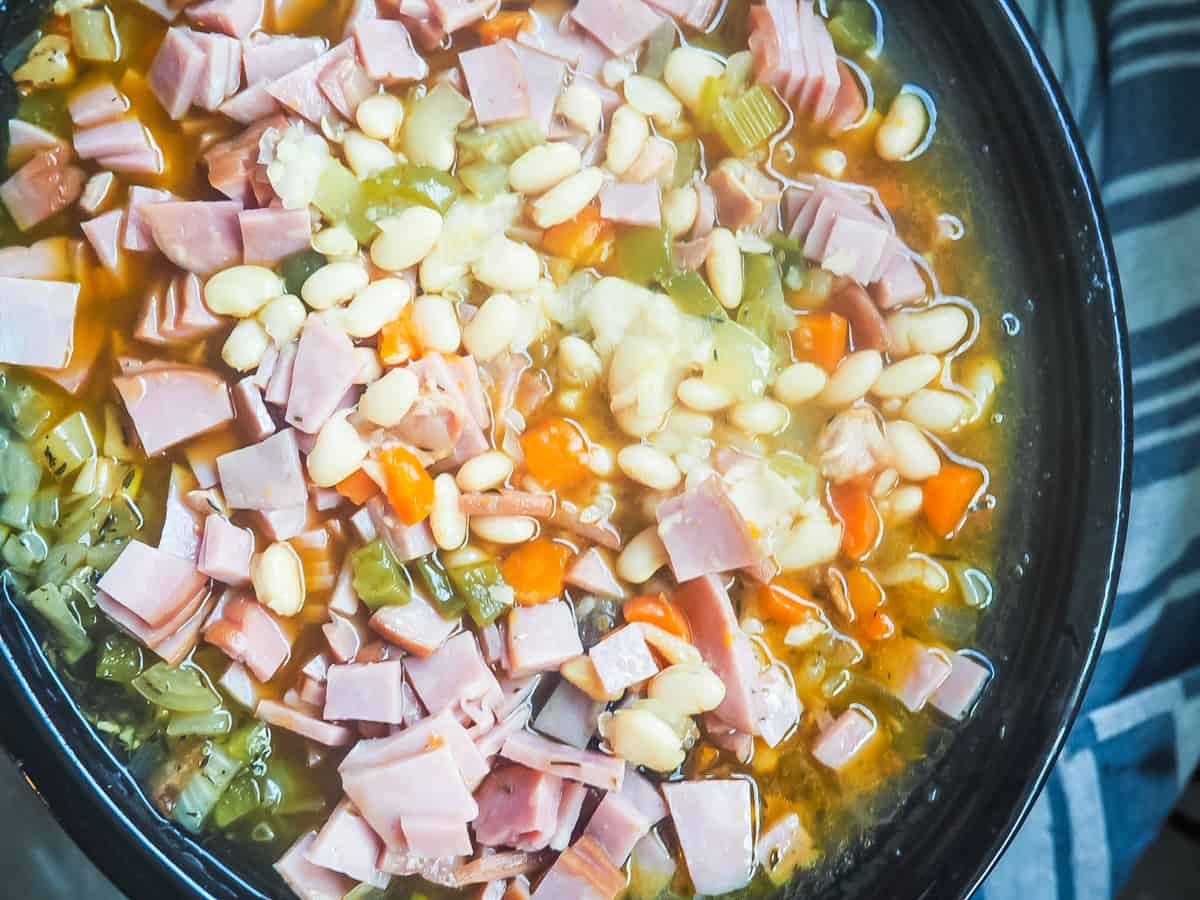 A crockpot filled with white beans and ham, cooking.
