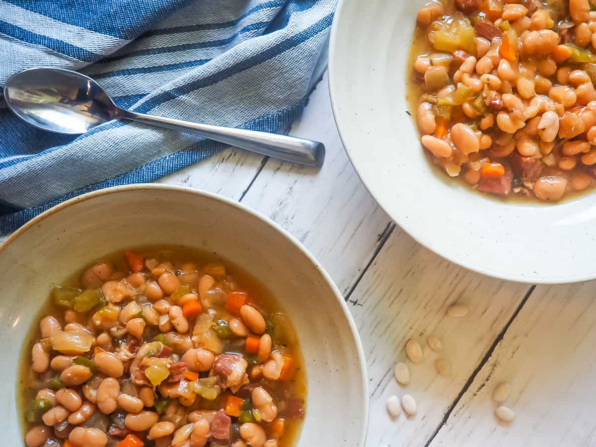 Two bowls of white beans and ham with a blue dish towel. and a bag of Camellia beans