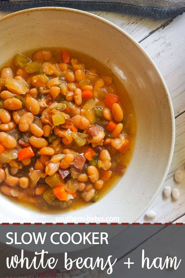 A pin image of a bowl of white beans and ham with Camellia beans spread around it.