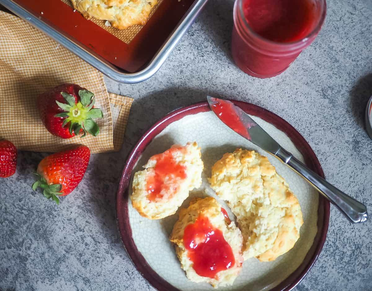 A biscuit cut in half with strawberry jam on a plate with a jar of jam and three strawberries.